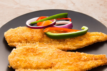 Fish Filet fried and served with sliced bell peppers and onions.