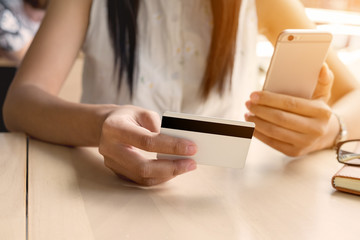 Beautiful woman hands holding a credit card and using smart phone for online shopping