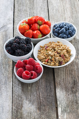 muesli and garden berries on wooden background, vertical