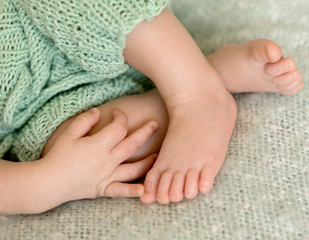 lovely tiny crossed baby legs out of pants and hand on them, closeup
