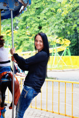 girl in a park rides on the carousel