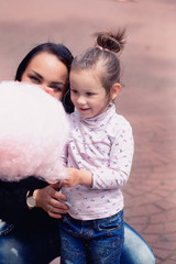 Mom and daughter in the park eating cotton candy