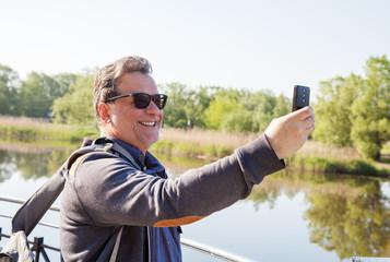elderly man makes selfie mobile phone