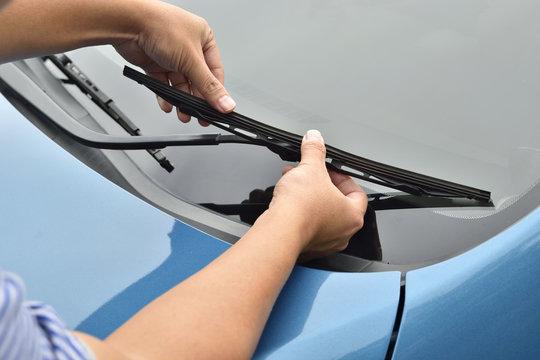man hand picking up windscreen wiper