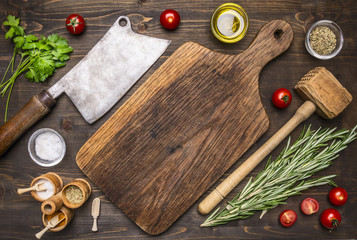 old cutting board with spices and herbs for cooking meat with cherry tomatoes and meat ax place for text,frame
