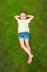 Smiling small happy girl relaxing on green grass. Summer time weekend mood. Templates t-short no print, you can place your own print or text.  Top view.