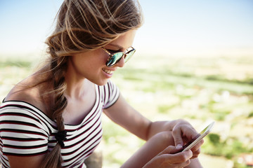 Beautiful portrait of happy smiling woman using smartphone on the top of the hill. Concept of tourism, connection and lifestyle.