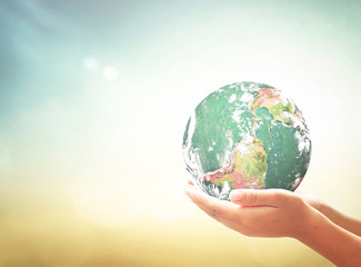 World environment day concept: Earth globe in human hands over blurred nature background. Elements of this image furnished by NASA
