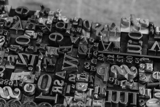 Metal Letterpress Types. A background from many historic typographical letters in black and white with white background.