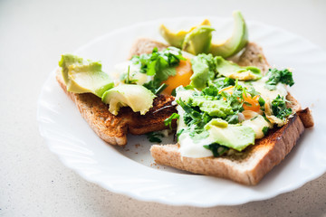 two eggs on toasts with avocado