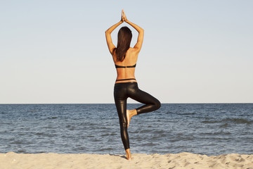 Young beautiful woman doing yoga on beach in black sport costume