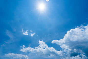 Bright sunshine with sun flares and clouds on clear blue sky background, hot summer concept