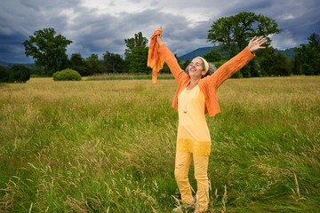 Happy mature woman standing countryside arms outstretched