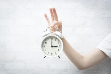 目覚まし時計を持った女性