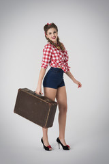 Sexy pin up with heavy suitcase