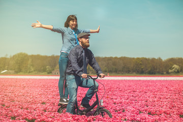 Couple cycling through tulip field