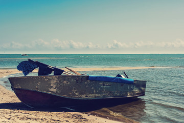 Old boat on the beach in a summer day