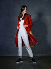 Fashion model wearing design red coat and white overalls posing in studio