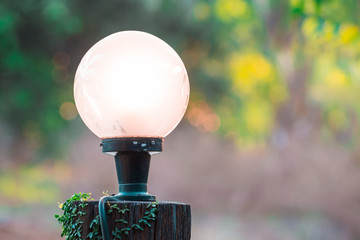 Lamp on old wooden pole in the garden. vintage style