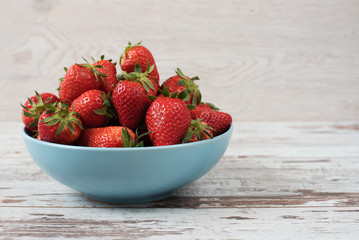 Pile of juicy ripe organic fresh strawberries in a large blue bowl. Light rustic wooden background