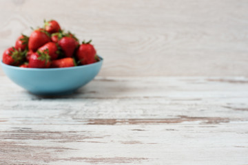 Blurred effect background. Pile of juicy ripe organic fresh strawberries in a large blue bowl. Light rustic wooden background.