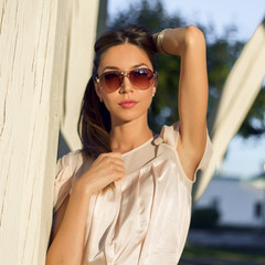 Outdoor fashion portrait glamor sensual young stylish woman in glasses, wearing a delicate summer dress outfit brunette girl. Pink , red lips tanned skin. Business lady resting .