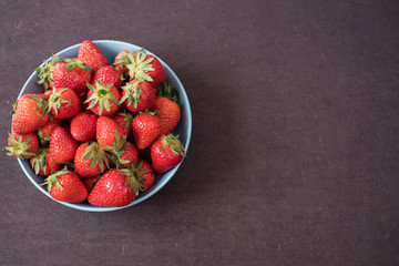 Pile of juicy ripe organic fresh strawberries in a large blue bowl. Dark background. Empty space