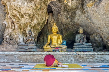 Asian woman pilgrim prostrating oneself in front of the Buddha statues at cave of Wat Tham Khao Wong. The cave is at Buddhist temple area in Uthai Thani, Thailand.