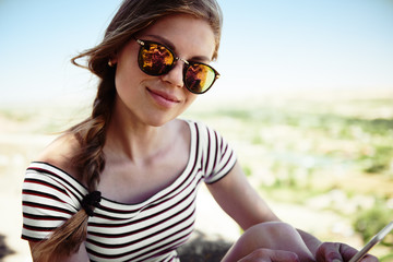 Young hipster woman resting on top of the mountain. Concept of hiking, holidays and tourism.
