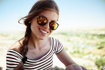 Portrait of pretty smiling girl in casual outfit and fashionable sunglasses. Concept of happiness, youth and lifestyle.