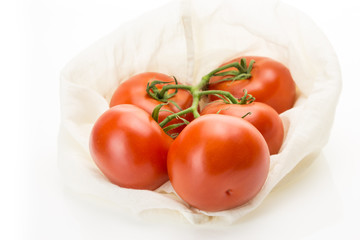 Fresh tomatoes in eco cloth bag, on white background