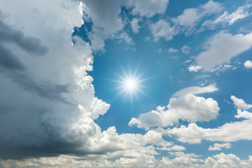 Blue sky with dark storm clouds and sun reflection