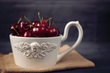 A large cup of coffee in front angel, white bowl full with fresh cherries, fruits. Dark rustic background, shabby chic, vintage tinting