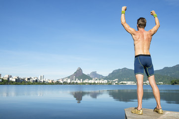 Athlete in blue compression shorts standing with champion arms raised in front of Rio de Janeiro, Brazil skyline at Lagoa Rodrigo de Freitas lagoon
