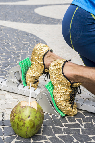 520ec295292ab2 Brazilian athlete in gold running shoes crouching with a coconut at the start  position in running