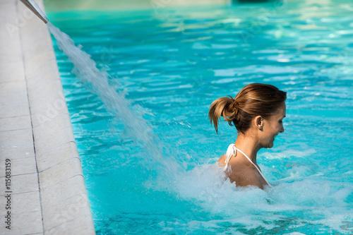 femme souriant dans une piscine sous un jet d 39 eau fotos. Black Bedroom Furniture Sets. Home Design Ideas
