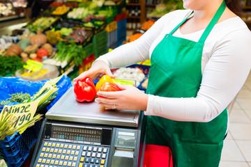 Verkäuferin wiegt Gemüse auf Waage im Laden