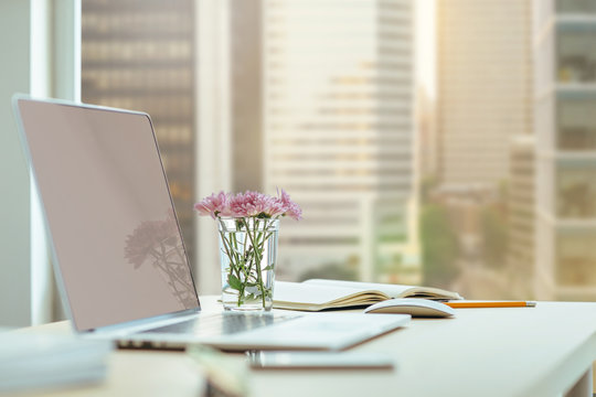 Modern blogger's workplace, Close-up desktop with modern laptop, flowers on the wooden desk. Desktop with a view of downtown, Sunrise, Shallow DOF. Workplace in a skyscraper.
