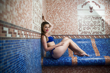 Beautiful young blonde caucasian woman in bikini relaxing in turkish bath at spa center