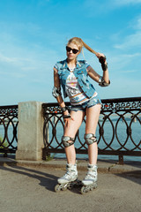 Young fit women girl in sunglasses, jeans shorts and a jacket on roller skates riding outdoors on river embankment, on the promenade