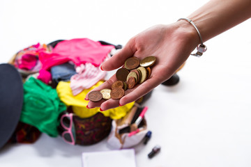 Girl's hand with coins. Open suitcase in the background. Chance to take a journey. New life far from home.
