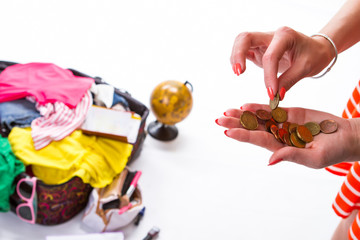 Lady's hand takes a coin. Opened bag with clothes. Money saved for a trip. Hands with orange manicure.