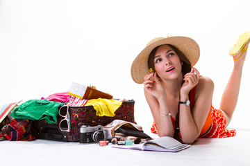Woman lays near overfilled suitcase. Girl with pen and notepad. Write a story about travelling. Remember the funniest things.