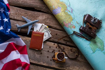 Brown passport and US flag. Photo camera on a map. Spend your vacation abroad. Visa to USA is opened.
