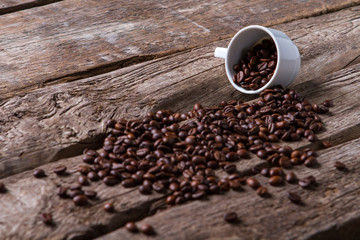 Roasted coffee beans and cup. Coffee grains on wooden surface. Best sort of coffee. Energy and taste.