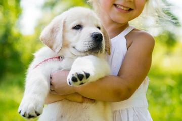 Little girl with a Golden retriever puppy Wall mural