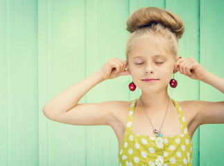 Beautiful girl holding cherries as earrings -style Rockabilly.