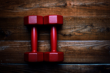 Two red dumbbells on a wooden background