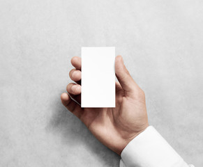 Hand holding blank vertical white business namecard mock up. Clear calling card mockup template hold arm. Visiting pasteboard paper surface display front. Small pure offset card holder presentation