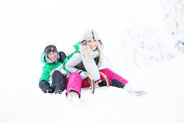Pärchen im Skigebiet auf dem Schlitten